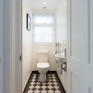 Idee per un piccolo bagno di servizio minimal con pistrelle in bianco e nero, pareti bianche, pavimento in gres porcellanato, lavabo sospeso e WC a due pezzi