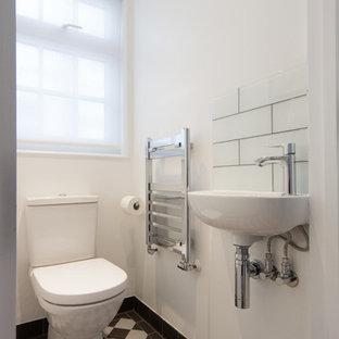 Diseño de aseo actual, pequeño, con sanitario de una pieza, baldosas y/o azulejos blancas y negros, paredes blancas, suelo de baldosas de porcelana, lavabo suspendido y baldosas y/o azulejos de vidrio laminado