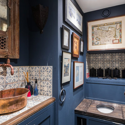 Powder room - small mediterranean multicolored tile powder room idea in London with blue cabinets, blue walls, a vessel sink, tile countertops, a one-piece toilet and multicolored countertops