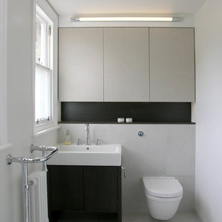 Photo of a contemporary cloakroom in London with an integrated sink, flat-panel cabinets, a wall mounted toilet, grey tiles and white walls.