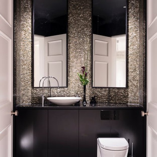 Design ideas for a large contemporary cloakroom in Surrey with flat-panel cabinets, black cabinets, a wall mounted toilet, mosaic tiles, marble flooring, marble worktops, black floors, a vessel sink, black worktops and multi-coloured tiles.