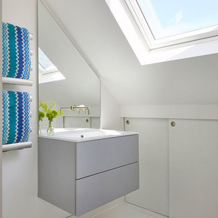 This is an example of a contemporary cloakroom in London with flat-panel cabinets, grey cabinets, white walls, a console sink and white floors.