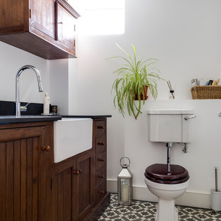 This is an example of a classic cloakroom in Wiltshire with freestanding cabinets, dark wood cabinets, white walls, a two-piece toilet and multi-coloured floors.