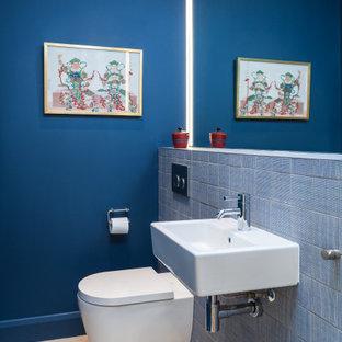 Immagine di un piccolo bagno di servizio minimalista con WC sospeso, piastrelle blu, piastrelle in ceramica, pareti blu, pavimento in pietra calcarea, lavabo sospeso, top piastrellato, pavimento beige e top blu