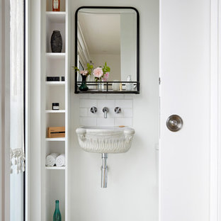 This is an example of an eclectic cloakroom in London with white walls, a wall-mounted sink and multi-coloured floors.