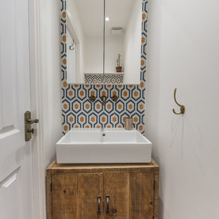 Inspiration för medelhavsstil toaletter, med släta luckor, skåp i mellenmörkt trä, blå kakel, orange kakel, vit kakel, vita väggar och ett fristående handfat