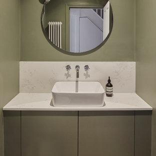 Ejemplo de aseo nórdico con armarios con paneles lisos, puertas de armario verdes, paredes verdes, suelo de madera en tonos medios, lavabo sobreencimera y encimeras blancas