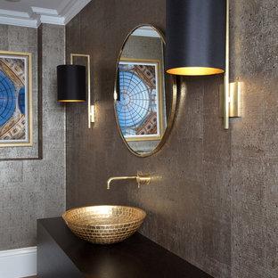 ロンドンの中くらいのモダンスタイルのおしゃれなトイレ・洗面所 (濃色木目調キャビネット、茶色いタイル、大理石タイル、茶色い壁、磁器タイルの床、横長型シンク、木製洗面台、茶色い床、ブラウンの洗面カウンター) の写真