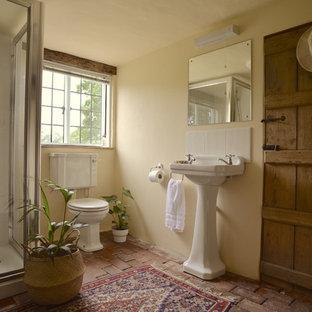 Пример оригинального дизайна: маленький туалет в стиле кантри с раздельным унитазом, белыми стенами, кирпичным полом и раковиной с пьедесталом