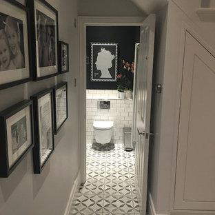Aménagement d'un petit WC et toilettes victorien avec un WC suspendu, des carreaux de céramique, un mur noir, un sol en carrelage de céramique et un lavabo suspendu.