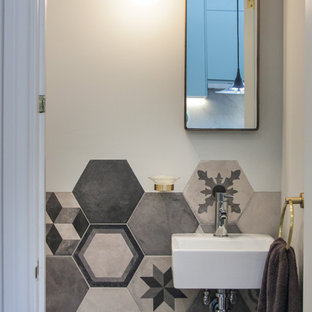 Photo of a small contemporary cloakroom in London with a wall mounted toilet, grey tiles, porcelain tiles, porcelain flooring, a wall-mounted sink and white walls.