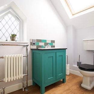 Design ideas for a midcentury cloakroom in London with shaker cabinets, turquoise cabinets, a two-piece toilet, grey walls, medium hardwood flooring, a console sink and brown floors.