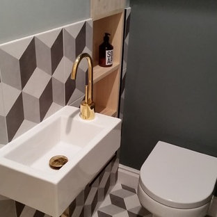 Small contemporary cloakroom in London with recessed-panel cabinets, light wood cabinets, multi-coloured tiles and a wall-mounted sink.