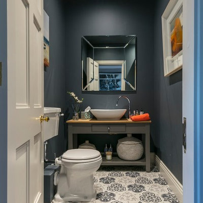 Example of a mid-sized trendy cement tile floor and multicolored floor powder room design in Dublin with open cabinets, gray cabinets, a two-piece toilet, gray walls, wood countertops and brown countertops