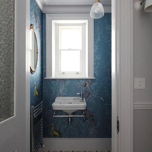 Inredning av ett modernt litet badrum, med en toalettstol med separat cisternkåpa, blå väggar, klinkergolv i keramik, ett väggmonterat handfat och flerfärgat golv