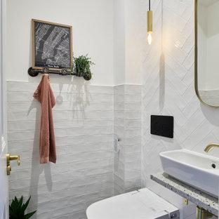 На фото: маленький туалет в стиле современная классика с инсталляцией, белой плиткой, белыми стенами, настольной раковиной, столешницей терраццо, разноцветным полом, серой столешницей и подвесной тумбой