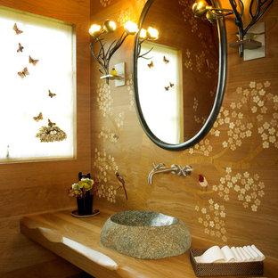 Modelo de aseo de estilo zen con lavabo sobreencimera, armarios abiertos, puertas de armario de madera oscura, encimera de madera y encimeras marrones