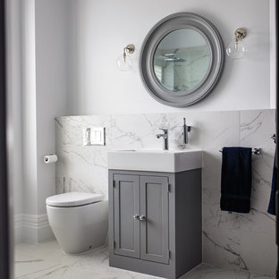 Inspiration for a traditional cloakroom in Surrey with shaker cabinets, grey cabinets, a one-piece toilet, white tiles, white walls, marble tiles, ceramic flooring and white floors.