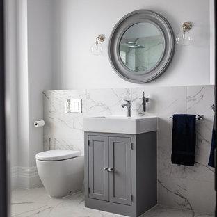 Exemple d'un WC et toilettes chic avec un placard à porte shaker, des portes de placard grises, un WC à poser, un carrelage blanc, un mur blanc, un plan de toilette blanc, du carrelage en marbre, un sol en carrelage de céramique et un sol blanc.