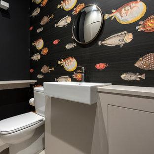 Diseño de aseo exótico con puertas de armario grises, sanitario de dos piezas, paredes multicolor y lavabo suspendido