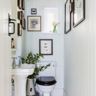 Small classic cloakroom in Dorset with a one-piece toilet, white walls, light hardwood flooring, a pedestal sink and beige floors.