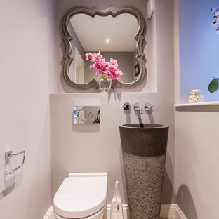 Design ideas for a classic cloakroom in London with a wall mounted toilet, grey walls, light hardwood flooring and an integrated sink.
