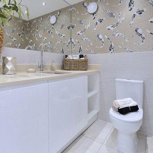 Свежая идея для дизайна: маленький туалет в современном стиле с плоскими фасадами, белыми фасадами, унитазом-моноблоком, врезной раковиной и белым полом - отличное фото интерьера