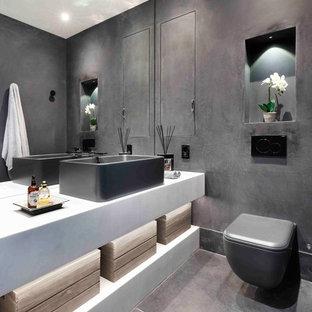 Modelo de aseo contemporáneo con paredes negras, suelo de pizarra, suelo negro, armarios abiertos, puertas de armario amarillas, sanitario de pared, lavabo sobreencimera y encimeras blancas