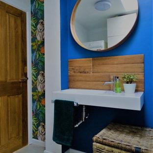 Foto di un piccolo bagno di servizio bohémian con piastrelle marroni, piastrelle effetto legno, pareti blu, pavimento con piastrelle in ceramica, lavabo sospeso, pavimento beige, mobile bagno sospeso e carta da parati