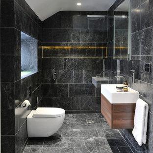 Ejemplo de aseo actual con armarios con paneles lisos, puertas de armario de madera oscura, sanitario de pared, lavabo sobreencimera y baldosas y/o azulejos de mármol
