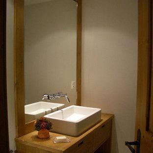 Новые идеи обустройства дома: туалет среднего размера в стиле современная классика с раковиной с несколькими смесителями, светлыми деревянными фасадами, полом из известняка, белыми стенами, столешницей из дерева и белым полом