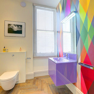 This is an example of a large contemporary cloakroom in London with a wall mounted toilet, multi-coloured walls, light hardwood flooring, a wall-mounted sink, glass worktops and beige floors.