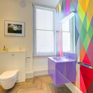 Cette photo montre un grand WC et toilettes tendance avec un WC suspendu, un mur multicolore, un sol en bois clair, un lavabo suspendu, un plan de toilette en verre, un sol beige et un plan de toilette violet.