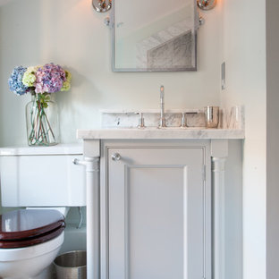 This is an example of a classic cloakroom in London with beaded cabinets, white cabinets, white walls, marble worktops and white worktops.