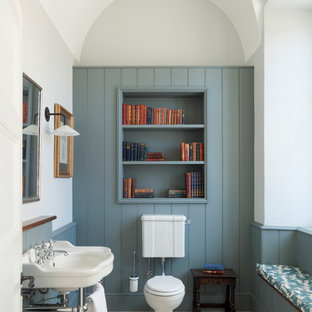 Small traditional powder room in London with a two-piece toilet, multi-coloured walls, a console sink, blue cabinets and beige floor.
