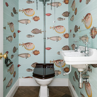 This is an example of a beach style powder room in London with a two-piece toilet, multi-coloured walls, dark hardwood floors and a wall-mount sink.