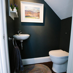 This is an example of a small contemporary cloakroom in London with a one-piece toilet and black walls.