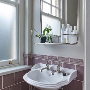 Exemple d'un WC et toilettes nature de taille moyenne avec un WC séparé, des carreaux de céramique, un mur violet, un sol en calcaire, un lavabo suspendu et un sol beige.