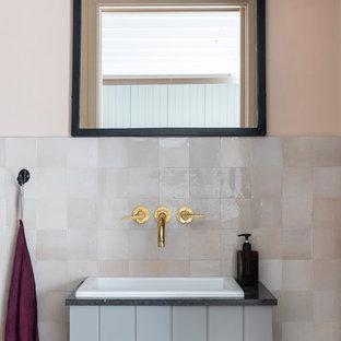 ロンドンのインダストリアルスタイルのおしゃれなトイレ・洗面所 (グレーのキャビネット、ピンクのタイル、ライムストーンの洗面台、黒い洗面カウンター、ピンクの壁) の写真
