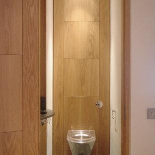ロンドンの小さいコンテンポラリースタイルのおしゃれなトイレ・洗面所 (フラットパネル扉のキャビネット、淡色木目調キャビネット、壁掛け式トイレ、緑のタイル、石タイル、白い壁、ライムストーンの床、オーバーカウンターシンク、ライムストーンの洗面台、緑の床、グリーンの洗面カウンター) の写真