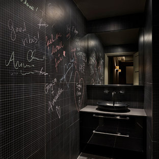 Design ideas for a medium sized contemporary cloakroom in London with flat-panel cabinets, black cabinets, black walls, slate flooring, a vessel sink and grey floors.