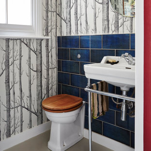 Inspiration for a bohemian cloakroom in London with a one-piece toilet, blue tiles, multi-coloured walls, a console sink and grey floors.