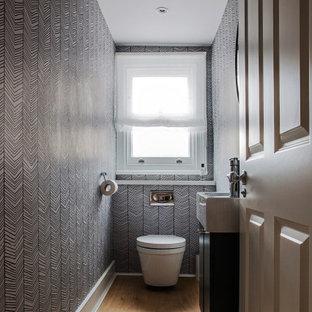 ロンドンの小さいコンテンポラリースタイルのおしゃれなトイレ・洗面所 (フラットパネル扉のキャビネット、黒いキャビネット、壁掛け式トイレ、淡色無垢フローリング、造り付け洗面台、壁紙) の写真