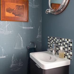Пример оригинального дизайна: маленький туалет в морском стиле с плоскими фасадами, серыми фасадами, синей плиткой, белой плиткой, синими стенами, монолитной раковиной и белой столешницей