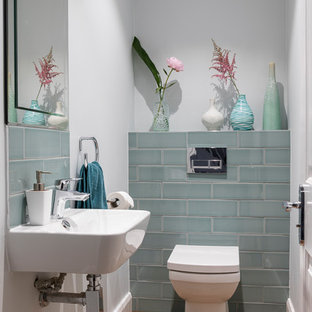 Small contemporary cloakroom in Other with a one-piece toilet, grey walls, medium hardwood flooring, a wall-mounted sink and brown floors.