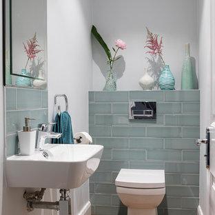 Idéer för små funkis toaletter, med en toalettstol med hel cisternkåpa, grå väggar, mellanmörkt trägolv, ett väggmonterat handfat och brunt golv