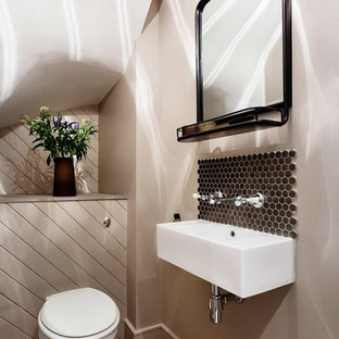 This is an example of a medium sized contemporary cloakroom in London with beige walls and a wall-mounted sink.
