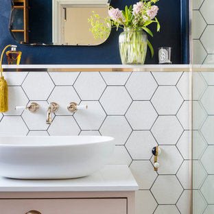 Photo of a classic cloakroom in London with flat-panel cabinets, white tiles, blue walls and a vessel sink.