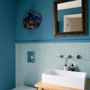 This is an example of a contemporary cloakroom in Other with a one-piece toilet, blue tiles, white tiles, matchstick tiles, blue walls, a vessel sink and wooden worktops.