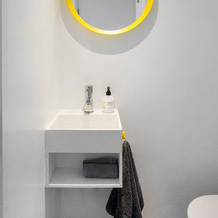 Photo of a small contemporary cloakroom in London with open cabinets, white cabinets, a wall mounted toilet, white walls, porcelain flooring, an integrated sink and grey floors.
